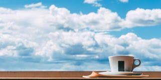 Une tasse de café devant un ciel nuageux Image stock