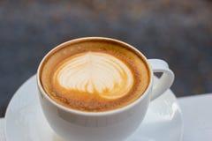 Une tasse de café en verre blanc, café d'art de Latte sur la table photo stock