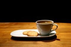 Une tasse de café et de biscuits chauds a servi sur le Tableau en bois du ` s de café sur le fond noir, avec l'espace libre pour  Photo libre de droits