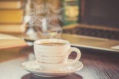Une tasse de café et bonjour de fumée au bureau au travail Image libre de droits