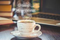 Une tasse de café et bonjour de fumée au bureau au travail Image stock