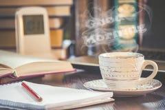 Une tasse de café et bonjour de fumée au bureau au travail Images stock