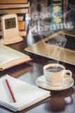 Une tasse de café et bonjour de fumée au bureau au travail Photographie stock libre de droits