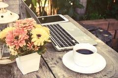 Une tasse de café et d'ordinateur portable sur le plancher en bois avec la fleur photo stock