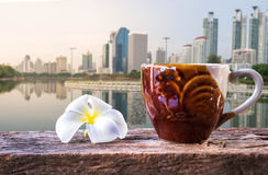 Une tasse de café et de plumeria sur la table en bois avec le fond de ciel bleu Images stock