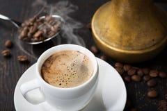 Une tasse de café et de grains de café frais aromatiques image libre de droits