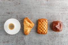 Une tasse de café et de petits pains dans une rangée sur un fond en bois Photos libres de droits