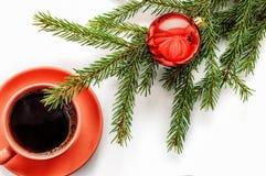 Une tasse de café et un arbre avec un jouet sur un fond blanc Photographie stock libre de droits