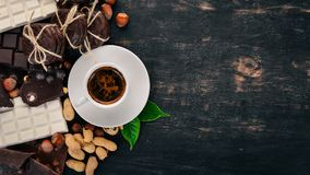 Une tasse de café et un ensemble de chocolat avec des biscuits et des bonbons Sur un fond en bois noir Photographie stock