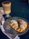 Une tasse de café frais avec des croissants sur un fond bleu-foncé, foyer sélectif images libres de droits