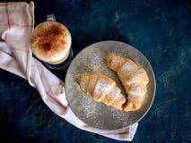 Une tasse de café frais avec des croissants sur un fond bleu-foncé, foyer sélectif photos stock