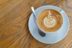 Une tasse de café de latte avec le modèle de fleur dans une tasse blanche sur le fond en bois Photo stock