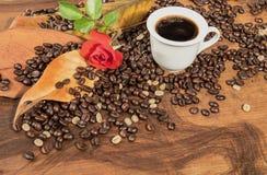 Une tasse de café noir avec les grains de café et la rose de rouge Image libre de droits
