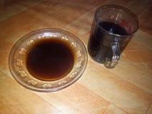 Une tasse de café noir est bue avec un tapis de tasse photos stock