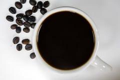 Une tasse de café noir et d'aucun sucre avec les grains de café rôtis dessus Photo libre de droits