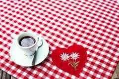 Une tasse de café noir sur un textile à carreaux de nappe Photos libres de droits