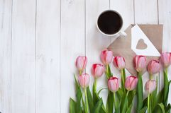 Une tasse de café noir, de téléphone et de tulipes roses Images libres de droits