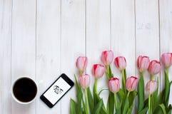 Une tasse de café noir, de téléphone et de tulipes roses Image libre de droits