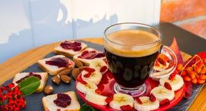 Une tasse de café, pain avec la confiserie, amandes, banane, baies photos libres de droits