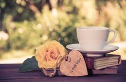 Une tasse de café parfumé et une pile de livres dans le jardin Image stock
