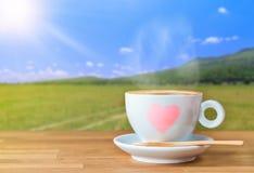 Une tasse de café sur la table en bois avec le fond de nature de tache floue Photographie stock libre de droits