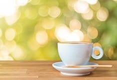 Une tasse de café sur la table en bois avec la lumière et le fond de bokeh Photos libres de droits
