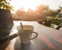 Une tasse de café sur la table en bois, la photo et la lumière chaude t de silhouette Image libre de droits