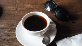 Une tasse de café sur la table et les sunglasseses Photos stock
