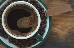 Une tasse de café sur une soucoupe avec des grains de café rôtis et un morceau de chocolat photographie stock libre de droits