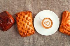 Une tasse de café sur une soucoupe et des gâteaux dans une rangée sur un backgro gris Photographie stock