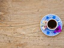 Une tasse de café turc avec des bonbons et des épices sur un surfa en bois Image libre de droits