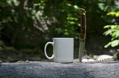 Une tasse de café vide et un couteau de mâle image stock