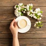Une tasse de caf? aromatique chaud dans des mains femelles et une branche de floraison de pommier sur un fond en bois Disposition photographie stock libre de droits