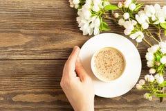 Une tasse de caf? aromatique chaud dans des mains femelles et une branche de floraison de pommier sur un fond en bois Disposition photo libre de droits