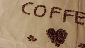 Une tasse de caf? aromatique est plac?e sur le papier de m?tier avec le mot ?caf? ?pr?sent? des grains de caf? banque de vidéos