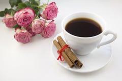 Une tasse de cannelle et de roses de café sur une porcelaine blanche de fond photo stock