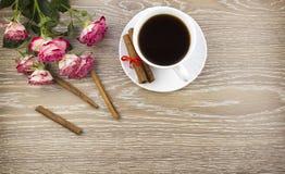 Une tasse de cannelle et de roses de café sur un vintage en bois de fond images libres de droits