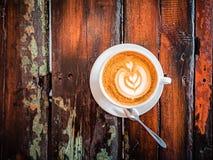 Une tasse de cappuccino sur une table dans un caf? Belle feuille de dessin d'usine sur la mousse de café de Latte Vue de ci-avant photographie stock libre de droits