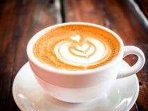 Une tasse de cappuccino sur une table dans un caf? Belle feuille de dessin d'usine sur la mousse de café de Latte Vue de ci-avant images libres de droits