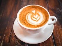 Une tasse de cappuccino sur une table dans un caf? Belle feuille de dessin d'usine sur la mousse de café de Latte Vue de ci-avant image stock