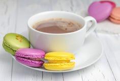 Une tasse de chocolat chaud avec les macarons colorés Images libres de droits