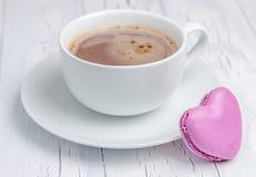 Une tasse de chocolat chaud avec un macaron en forme de coeur photographie stock libre de droits