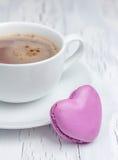 Une tasse de chocolat chaud avec un macaron en forme de coeur (vertical) Images stock