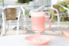 Une tasse de couleur de corail de latte sur la table du patio d'été photos libres de droits