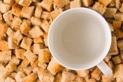 Une tasse de l'eau carbonatée parmi des biscottes Photo stock