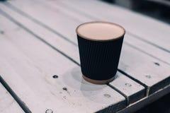 Une tasse de latte sur la table en bois élégante de cru photos stock