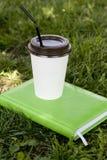 Une tasse de livre blanc avec une barre chaude noire de café ou de thé se tient sur a Photographie stock libre de droits