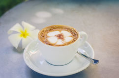 Une tasse de modèle de plumeria de café dans une tasse blanche sur le fond en bois Photos libres de droits