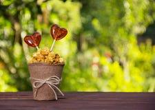 Une tasse de papier avec le maïs éclaté et la sucrerie de caramel Lucettes sous forme de coeur Photos stock