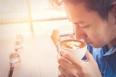 Une tasse de prise d'homme d'affaires de café dans le café photos stock